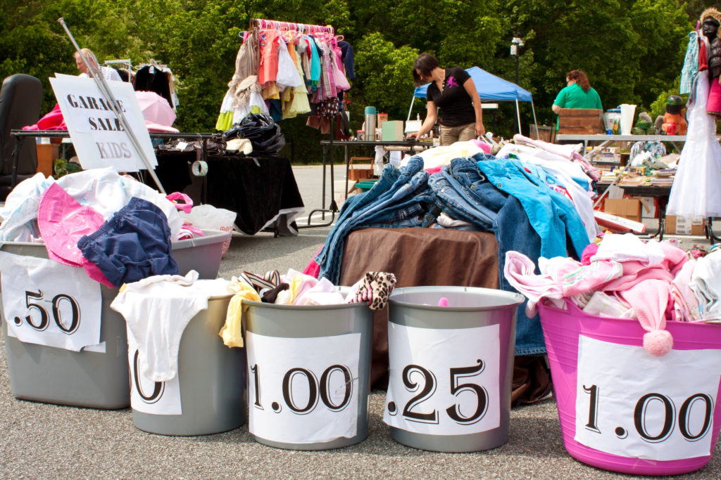 """Lilburn, GA, USA - April 21, 2012: Containers labeled with prices hold merchandise being sold in a parking lot at the Lilburn citywide garage sale"""