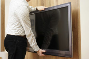 A man packing a flat screen tv in Perth